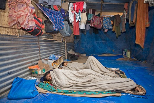Stock Photo: 1886-48085 Sick construction workers resting in their temporary corrugated sheet accommodation while their fellow workers are on the work site ; Ahmedabad ; Gujarat ;  India