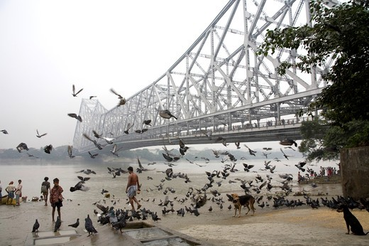 Activities on Babu ghat ; Howrah bridge over Hooghly river in background ; Calcutta now Kolkata ; West Bengal ; India : Stock Photo