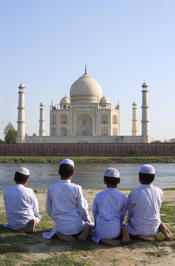 Stock Photo: 1886-50005 Young muslim boys performing religious prayer Namaz in front of Taj Mahal Seventh Wonders of World on south bank of Yamuna river ; Agra ; Uttar Pradesh ; India UNESCO World Heritage Site