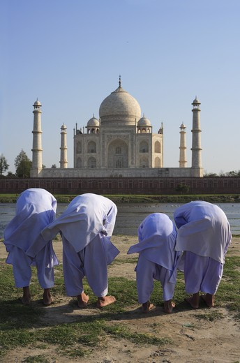 Stock Photo: 1886-50007 Young muslim boys performing religious prayer Namaz in front of Taj Mahal Seventh Wonders of World on south bank of Yamuna river ; Agra ; Uttar Pradesh ; India UNESCO World Heritage Site