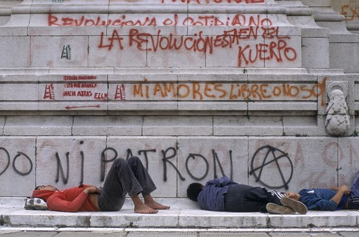 Stock Photo: 1886-50475 UNEMPLOYED street people in front of GRAFFITI which protests govenrment policies - BUENOS AIRES, ARGENTINA