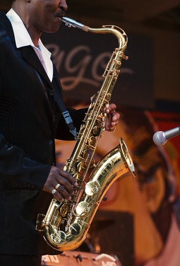 SAXOPHONIST Julien Vaught preforms with the J C SMITH BAND at the MONTEREY BAY BLUES FESTIVAL - MONTEREY, CALIFORNIA : Stock Photo