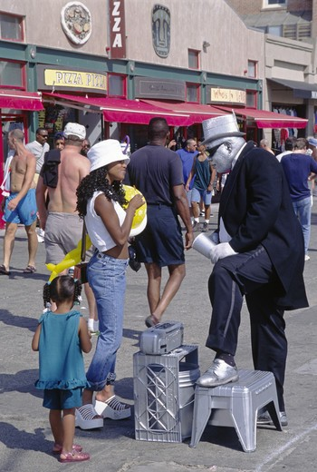 Stock Photo: 1886-50727 Entertainer talks with young African Americal woman  - VENICE BEACH, CALIFORNIA