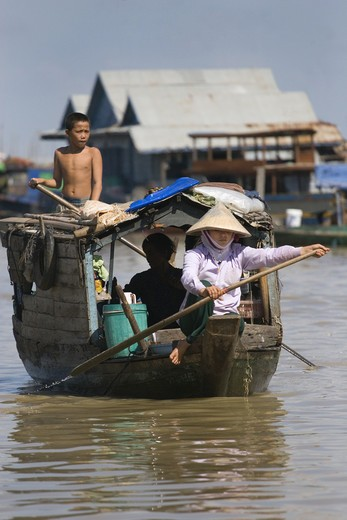 Stock Photo: 1886-51001 Polling a merchant boat in the Vietnamese floating village of Chong Kneas on lake Tonle Sap - Siem Reap, Cambodia