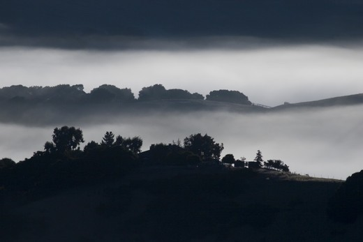 Early morning fog hangs in the low lands below Los Laureles Grade between Carmel Valley and the Salinas Valley - Coastal Mountain Range, California : Stock Photo