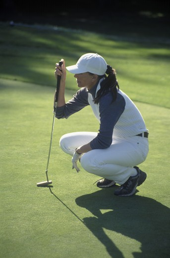 WOMAN GOLFER prepares to PUTT on the FOURTH HOLE of BAYONETTE GOLF COURSE at Fort Ord on the MONTEREY PENINSULA : Stock Photo