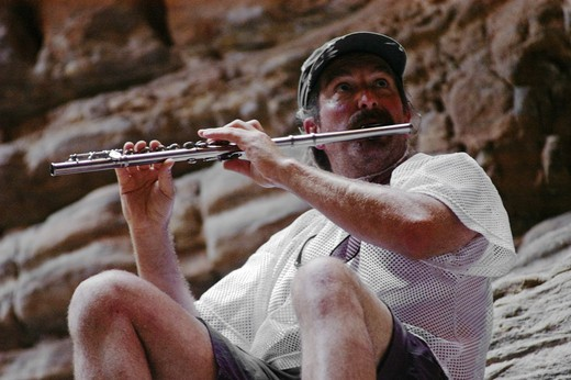 AMOS LOVELL plays flute in the slot canyon of BLACK TAIL CANYON NARROWS a truly spiritual experience - GRAND CANYON NATIONAL PARK, ARIZONA : Stock Photo