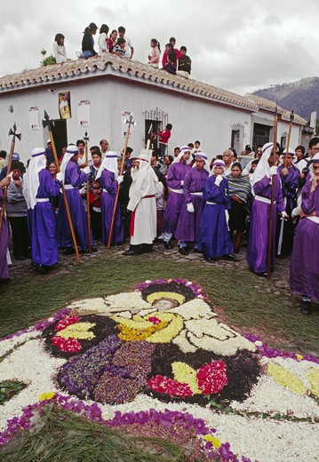 Purple-robed PENITENTS and ANGEL ALFOMBRA (carpet) made of sawdust and flowers for GOOD FRIDAY - ANTIGUA, GUATAMALA : Stock Photo