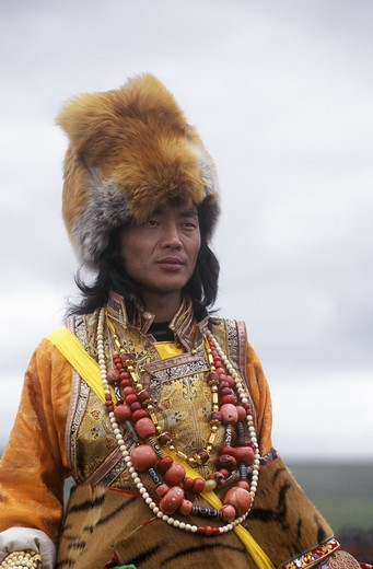 Stock Photo: 1886-52531 Male Khampa wears coral, zee stones, fox fur hat & tiger skin at the Litang Horse Festival - Sichuan Province, China, (Tibet)