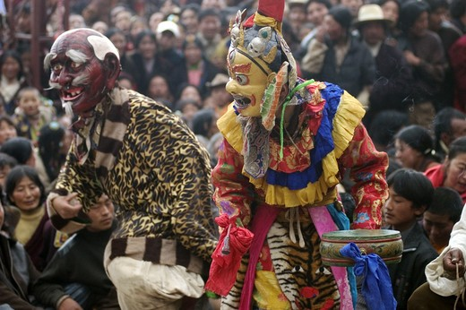 Stock Photo: 1886-52739 Masked dancer & clown entertain the crowd at the Monlam Chenmo masked dances, Katok Monastery - Kham, (Tibet), Sichuan, China