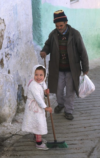 Stock Photo: 1886-53869 A young GIRL SWEEPS the cobblestones in the MEDINA in CHECHAOUEN in the RIF MOUNTAINS of northern MOROCCO