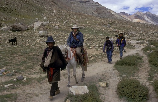 woman  rides a HORSE around MOUNT KAILASH (6638 M), the most sacred HIMALAYAN PEAK in TIBET : Stock Photo