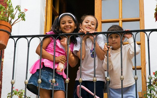 Three cute young MEXICAN GIRLS on a BALCONY - GUANAJATO, MEXICO : Stock Photo
