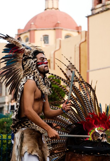 Stock Photo: 1886-56363 An AZTEC DANCER plays a DRUM dressed in a traditional warrior feathered COSTUME during the CERVANTINO FESTIVAL  - GUANAJUATO, MEXICO