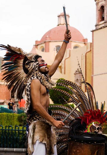 Stock Photo: 1886-56364 An AZTEC DANCER plays a DRUM dressed in a traditional warrior feathered COSTUME during the CERVANTINO FESTIVAL  - GUANAJUATO, MEXICO