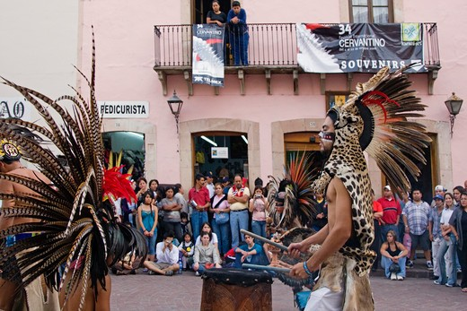 An AZTEC DANCER plays a DRUM dressed in a traditional warrior feathered COSTUME during the CERVANTINO FESTIVAL  - GUANAJUATO, MEXICO : Stock Photo