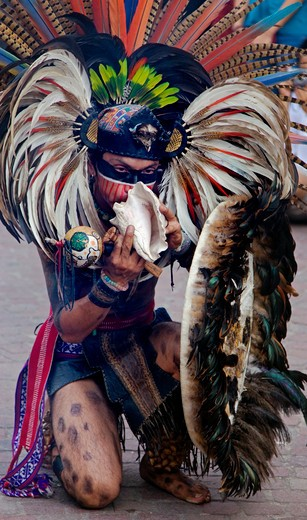 Stock Photo: 1886-56369 An AZTEC DANCER blows a CONCH in a traditional feathered warrior COSTUME during the CERVANTINO FESTIVAL - GUANAJUATO, MEXICO