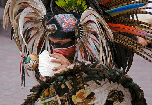 Stock Photo: 1886-56370 An AZTEC DANCER blows a CONCH in a traditional feathered warrior COSTUME during the CERVANTINO FESTIVAL - GUANAJUATO, MEXICO