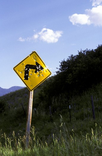 Stock Photo: 1886-56867 Right turn sign riddled with bullet holes, on a rural roadside in Montana.