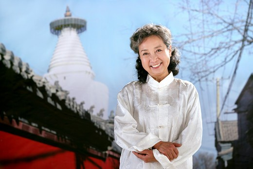 Stock Photo: 1886-60416 oriental senior woman beside the temple