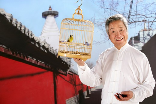 Stock Photo: 1886-60482 oriental senior man holding birdcage beside temple