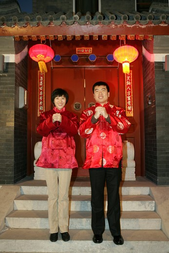 Stock Photo: 1886-61088 Chinese family gesturing welcome at the gate celebrating Chinese New Year