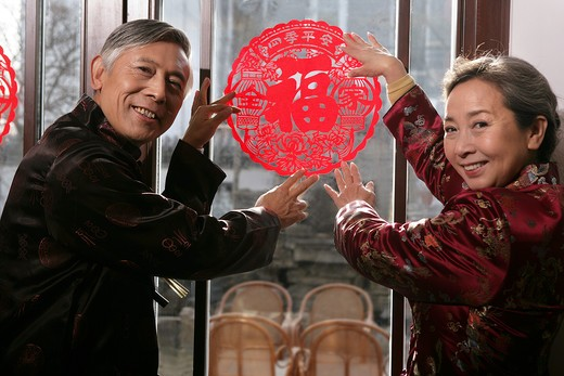 Stock Photo: 1886-61141 Chinese mature couple holding chinese cut paper on New year's Eve