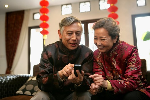Chinese mature couple making a phone call : Stock Photo