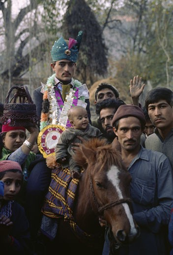 Stock Photo: 1886-6267 COSTUMED GROOM rides a HORSE to his brides home in AFAN VILLAGE during his WEDDING - KASHMIR, INDIA