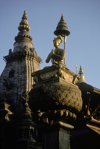 A bronze statue of king Bupathindra Malla sits on a stone pillar in Bhaktapurs's Durbar Square. : Stock Photo
