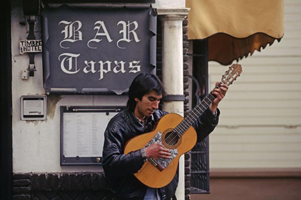Stock Photo: 1886-7020 A Spaniard plays FLAMENCO GUITAR outside a restaurant in SEVILLA - SPAIN