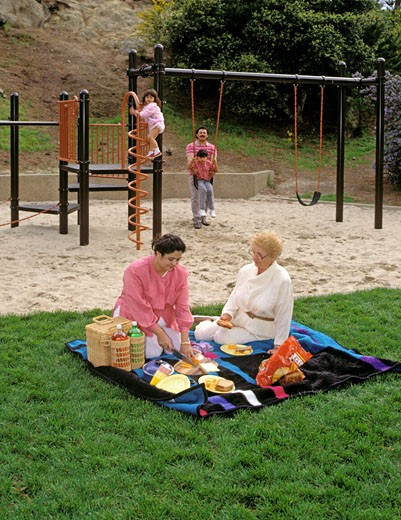 Stock Photo: 1886-7500 HISPANIC mother & grandmother set up PICNIC while father & children play on the PLAYGROUND