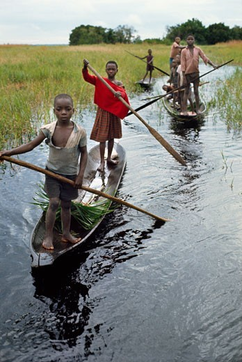 Children of Libinza tribe going to school by canoe, Ngiri river region, Democratic Republic of the Congo (ex-Zaire), Africa. : Stock Photo