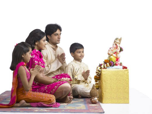 VDA200245 : South Asian Indian family with father, mother, son and daughter sitting praying to lord Ganesha wearing traditional dress kurta, pajama, pink and orange color dress, pink dress, MR # 698, 699, 700, 701 : Stock Photo