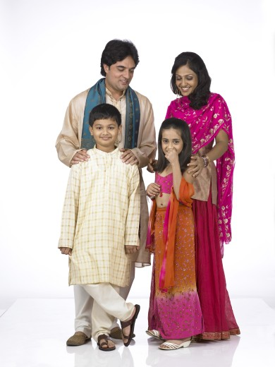 VDA200268 : South Asian Indian family with father, mother, son and daughter standing smiling, enjoying and looking at camera wearing traditional dress kurta, pajama, pink and orange color dress, pink dress, MR # 698, 699, 700, 701 : Stock Photo