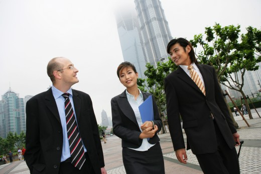 two businessmen and one businesswoman from different cultures talking under the Jinmao Tower,Shanghai,China : Stock Photo