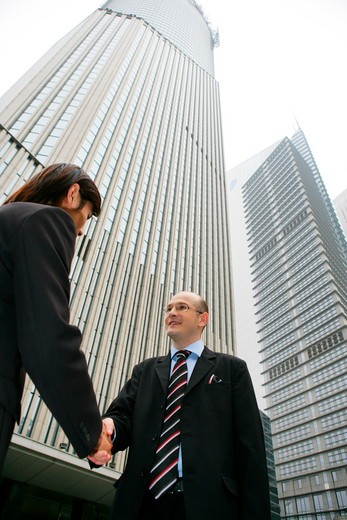 two businessmen from different cultures handshaking in the street in Shanghai,China : Stock Photo