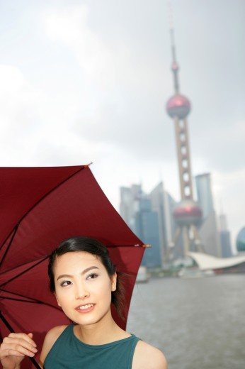 one young woman holding an opened umbrella at the Bund,Shanghai,China : Stock Photo