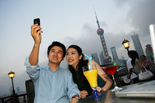 couple taking pictures of self with camera phone beside table on the Bund,Shanghai,China : Stock Photo