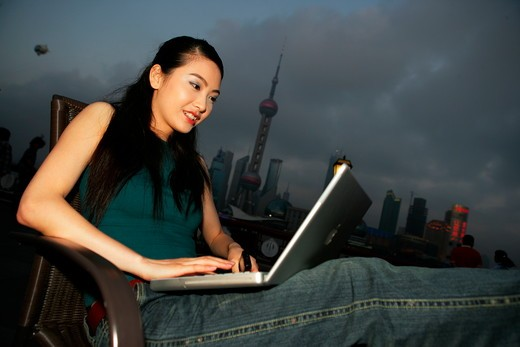 Stock Photo: 1886R-17658 young woman using laptop beside table at the Bund,Shanghai,China