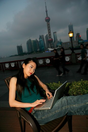 young woman using laptop beside table at the Bund,Shanghai,China : Stock Photo