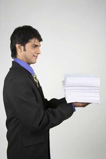Stock Photo: 1886R-24879 Executive holding bundle papers