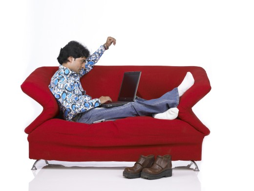 VDA200162 : South Asian Indian man sitting on sofa working on laptop wearing jeans and shirt, MR # 701 : Stock Photo