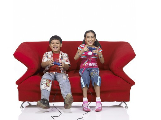 VDA200175 : South Asian Indian two children brother and sister sitting on sofa playing video game wearing jeans and shirt, MR #  699, 700 : Stock Photo