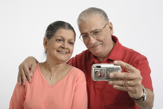 Old couple, senior citizens old man wearing red T Shirt, Specs, Spectacles, glasses, old lady wearing light tomato colour full sleeve top, gold chain with pendent, earrings Man holding digital camera in his hand and trying to click their photograph, MR # 703B and 703A : Stock Photo