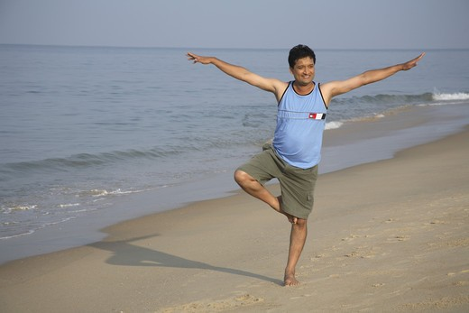 Stock Photo: 1886R-25199 South Asian Indian young man doing aerobics standing on one folded leg with spread hands both side on seashore ; Shiroda ;  Dist. Sindhudurga ; Maharashtra ; India MR#703D