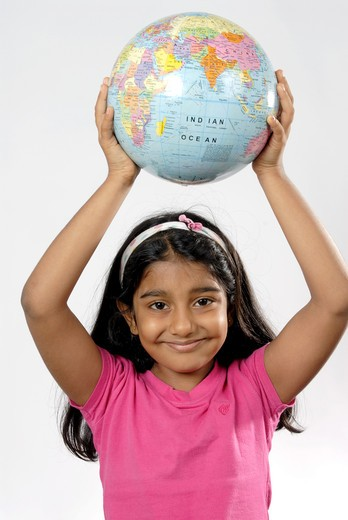 South Asian Indian girl holding globe above head and smiling MR#152 : Stock Photo