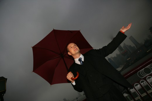 one caucasian businessman looking up with an opened umbrella at the Bund,overcast and rainy,Shanghai,China : Stock Photo