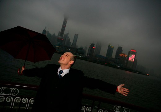 one caucasian businessman arms stretched with an opened umbrella at the Bund,overcast and rainy,Shanghai,China : Stock Photo