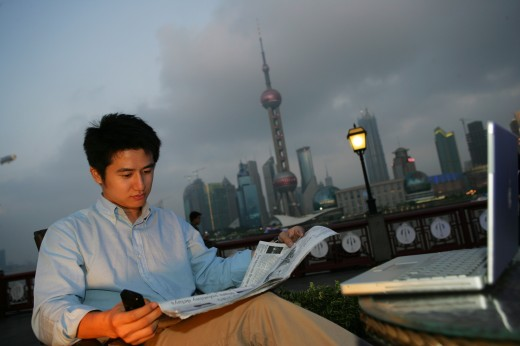 Stock Photo: 1886R-27510 one young man reading a newspaper beside a table on the Bund,Shanghai,China